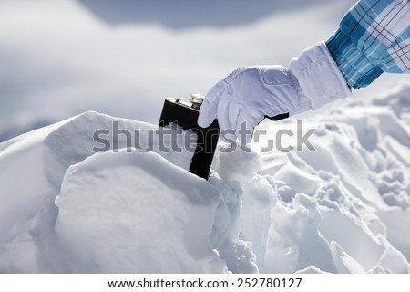 Hipflask in snow - stock photo