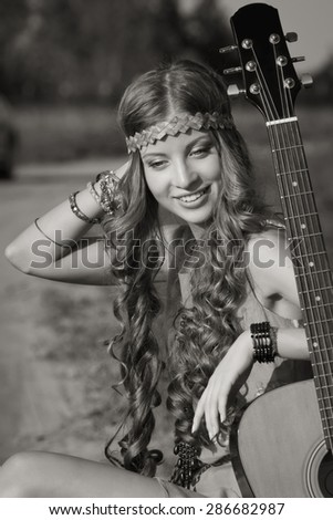 Hippie girl travelling with her guitar on a road - stock photo