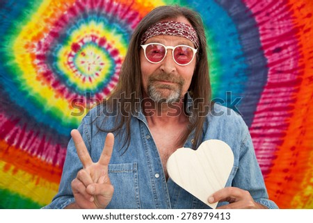 Hippie middle-aged peaceful man wearing red headband, sunglasses and blue denim shirt while making the victory sign and holding a white handmade heart shape, portrait on spiral colorful background - stock photo