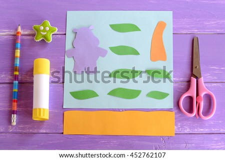 Hippo, leaves, palm tree trunk cut from colored paper. Set for children craft projects. Paper card hippo craft. Glue stick, scissors, pencil, eraser on wooden background. Kids tutorial. Step - stock photo