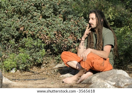 hippy preparing, rolling and smoking marijuana joint : photos series - stock photo