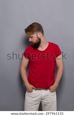 Hipster bearded man posing with his arms in pockets. Handsome man in red T-shirt looking away isolated on grey. - stock photo