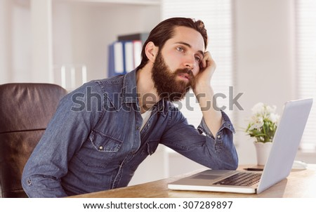 Hipster businessman bored at his desk in his office - stock photo