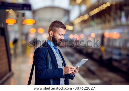 Hipster businessman with tablet, waiting, train platform - stock photo