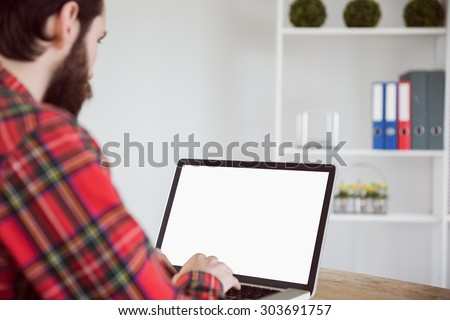 Hipster businessman working on his laptop in his office - stock photo