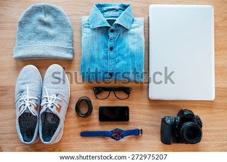 Hipster collection. Top view of clothing and diverse personal accessory for hipster laying on the wooden grain - stock photo