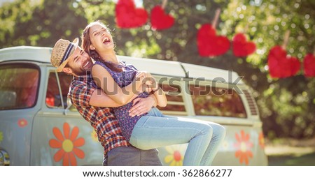 Hipster couple having fun together against hearts hanging on a line - stock photo