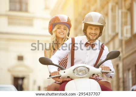 Hipster  couple riding a scooter on a sunny day in the city - stock photo