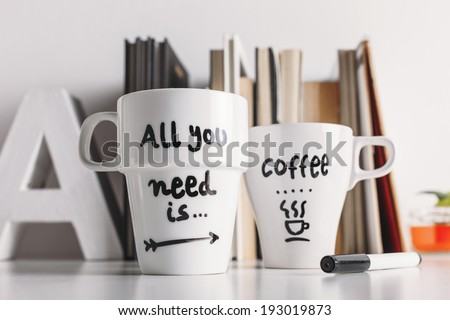 Hipster cup of coffee on a books library./ Close up of two white coffee mug with diy decoration.  - stock photo