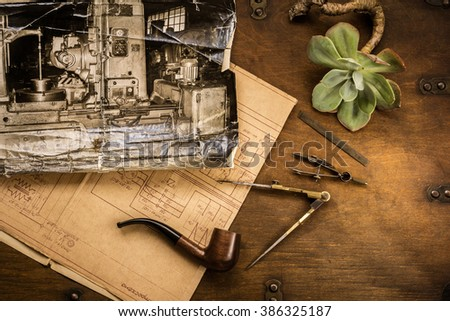 Hipster flat lay / top view.  Photograph of old machine, mechanical plane, pipe, tools (vintage compass set) , succulent plan in rustic wood - stock photo