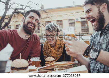 Hipster Friends In Fast Food Restaurant Eating Burgers - stock photo