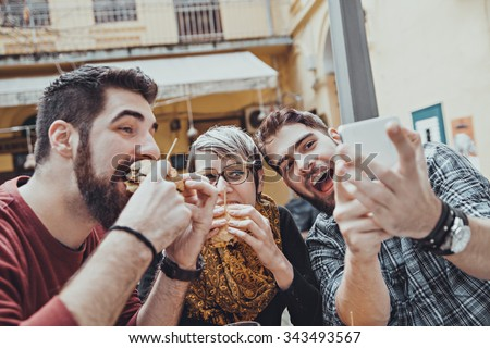 Hipster Friends In Fast Food Restaurant Taking Selfie While They Are Eating Burgers - stock photo