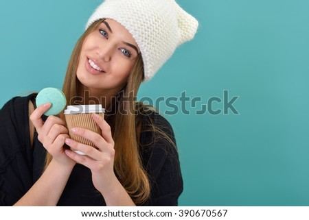 Hipster girl eating french macaron and coffee over turquoise background. Studio female portrait. Diet, sweets, cakes, eating. - stock photo
