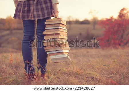 Hipster girl holding a stack of books - stock photo