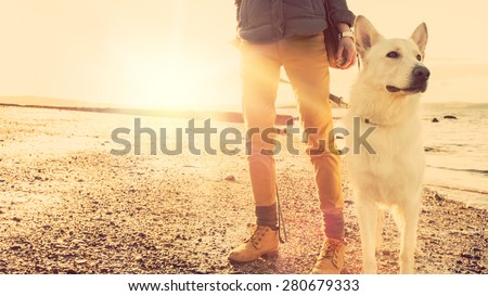 Hipster girl playing with dog at a beach during sunset, strong lens flare effect - stock photo