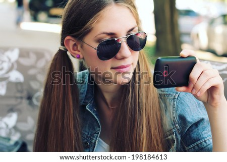 Hipster girl uses a smartphone. Photo toned style instagram filters - stock photo