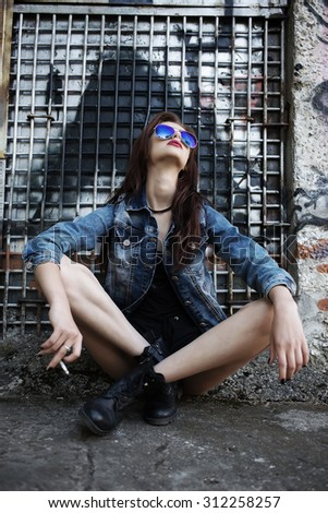 hipster girl with naked feet smoking looking up - stock photo