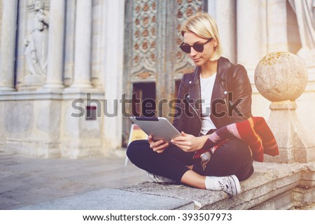 Hipster girl with trendy look is reading electronic book on portable touch pad, while is sitting outside the museum. Beautiful woman is watching movie on digital tablet, while relaxing after strolling - stock photo