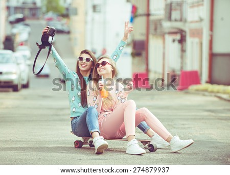 Hipster girlfriends taking a selfie in urban city context seat on skate - Concept of friendship and fun with new trends and technology - Best friends eternalizing the moment with modern digital camera - stock photo