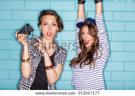 Hipster girls wearing stylish bright outfits going crazy and having great time. Standing together near blue brick wall with photo camera and have fun while taking selfie self portrait of each other. - stock photo