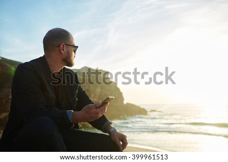 Hipster guy is listening to music on mobile phone, while is relaxing in spring vacation near ocean with copy space background. Beaded man in sunglasses is holding cell telephone and enjoying sea view - stock photo
