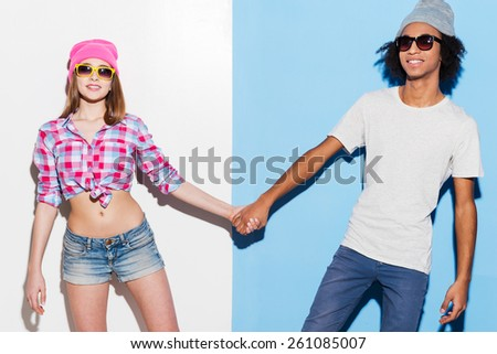 Hipster love. Funky young couple wearing sunglasses and smiling while standing against colorful background - stock photo