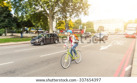 Hipster man cycling in London on a busy street. He is riding a fixed gear bike and wearing a helmet. Panning technique to blur cars and background. Transportation and lifestyle concepts. - stock photo