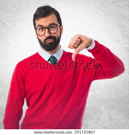 Hipster man doing bad signal over grey background - stock photo