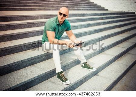 Hipster man hands holding digital tablet , business person browsing internet or connecting to wireless via touchscreen pad sitting outdoors - stock photo