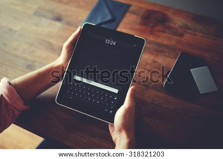 Hipster man hands holding digital tablet with empty blank screen for your text message, business person browsing internet or connecting to wireless via touchscreen pad sitting at brown wooden table - stock photo