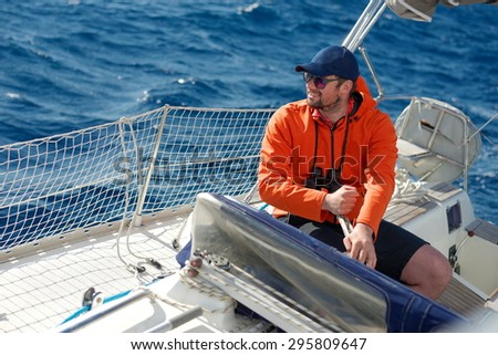 Hipster man sailing with sails out on a sunny day - stock photo
