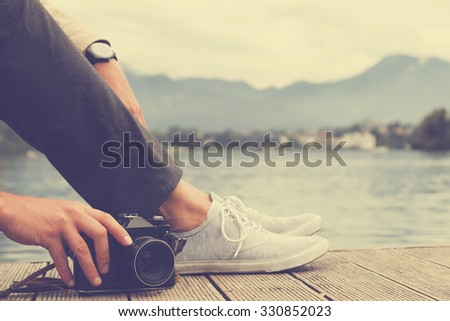 Hipster man taking photos with camera on the river. - stock photo