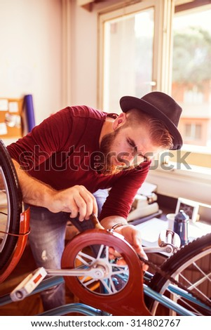 Hipster man working in bike workshop, cleaning bicycle chain  - stock photo