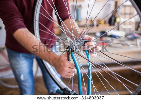 Hipster man working in bike workshop, fixing bicycle spokes - stock photo