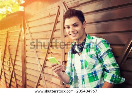 Hipster mixed race man with headphones and smart phone. Hispanic handsome young guy smiling. Outdoors summer leisure activity. - stock photo