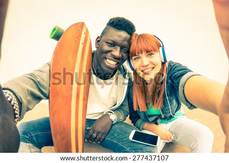 Hipster multiracial couple in love taking selfie on white background - Fun concept with alternative fashion and technology trends - Redhead girlfriend with afro american guy - Vintage filtered look - stock photo