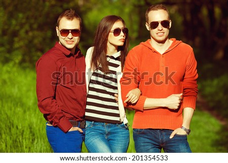 Hipster people concept. Portrait of fashionable friends in trendy casual clothing walking in the park together. Stylish eyewear. Sunny weather. Outdoor shot - stock photo