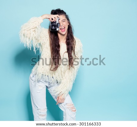 hipster photographer fashion stylish woman dancing and making photo using retro camera. Portrait on blue background in white sweater - stock photo