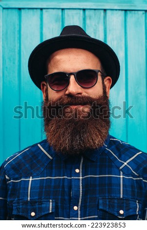 Hipster style bearded man wearing a black hat - stock photo