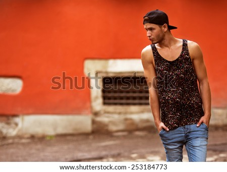 Hipster style guy. Fashion man standing near wall street orange