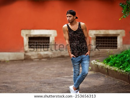 Hipster style guy. Fashion man standing near wall street orange  - stock photo
