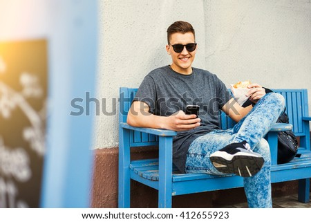 Hipster style guy with a fashionable hairdo. a young man sitting on a bench in the street, holding the phone, eating a sandwich bag and a lion, sunglasses, shoes, jeans, cap, boy laughs - stock photo