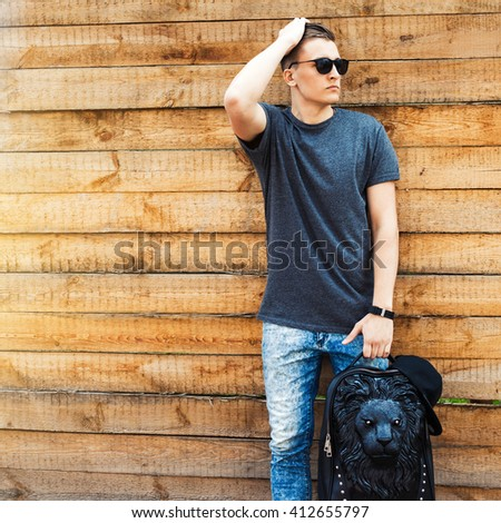 Hipster style. handsome young man with a fashionable hairdo. vintage photo. The guy standing near the old wooden wall. In the hands of a fashion backpack and a lion, sunglasses, sneakers, jeans - stock photo