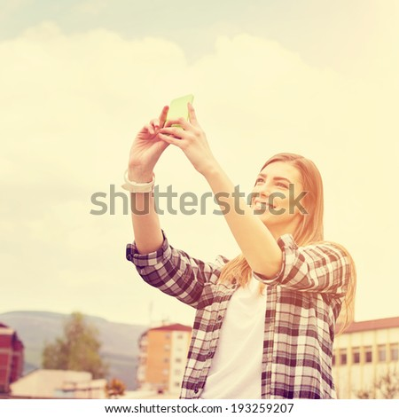 Hipster teenage Caucasian girl taking a selfie photograph with smart phone smiling. City urban scene in the background. Square image with instant filter applied. - stock photo
