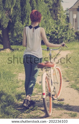 Hipster teenage girl with her vintage bicycle, enjoying beautiful sunny day. Retro styled imagery, toned image  - stock photo