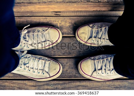 Hipster teenage tone styled image of white shoes facing couple - stock photo
