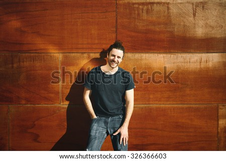 Hipster urban man portrait standing on city wall keeps the hand on his grey jeans smiling and looking at camera. Young adult enjoying sunny holidays under the sun. Young Caucasian man his twenties.  - stock photo