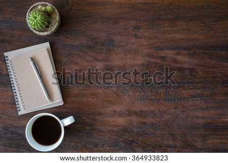Hipster vintage office desk table with notebooks, pen and a cup of coffee. Top view with copy space. - stock photo