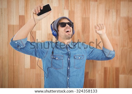 Hipster wearing sunglasses enjoying music against wooden wall - stock photo