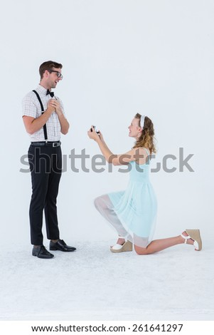 Hipster woman doing a marriage proposal to her boyfriend on white background - stock photo